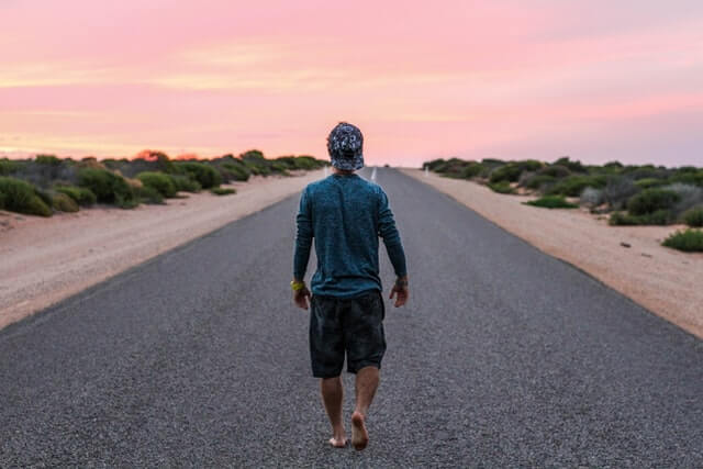 Man walking alone on the road at sunset
